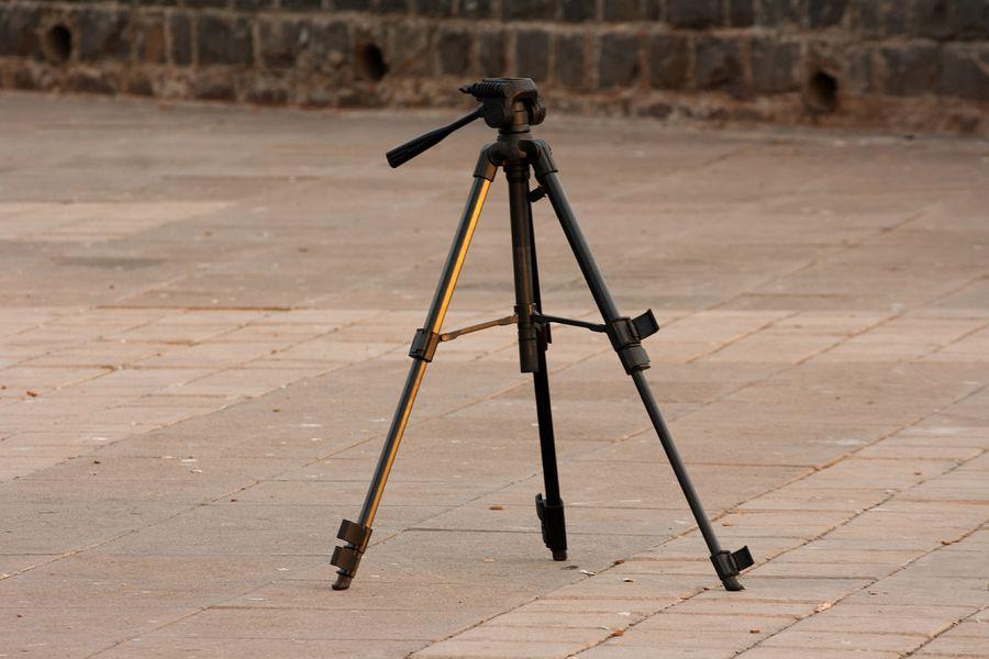 Camera tripod placed on a pavement