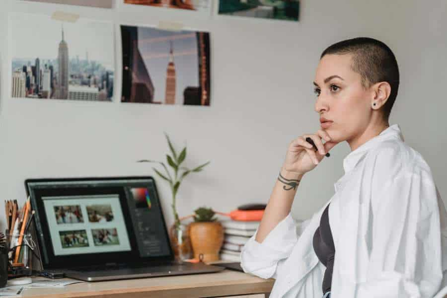Woman pensive, as she sits in front of her laptop