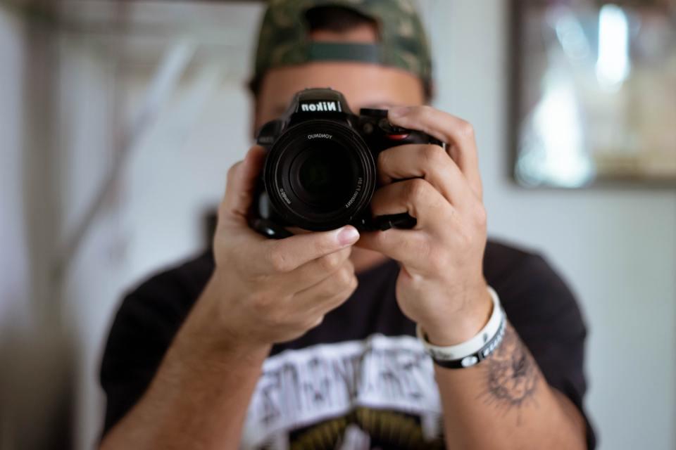 Selective focus of man holding a Nikon camera