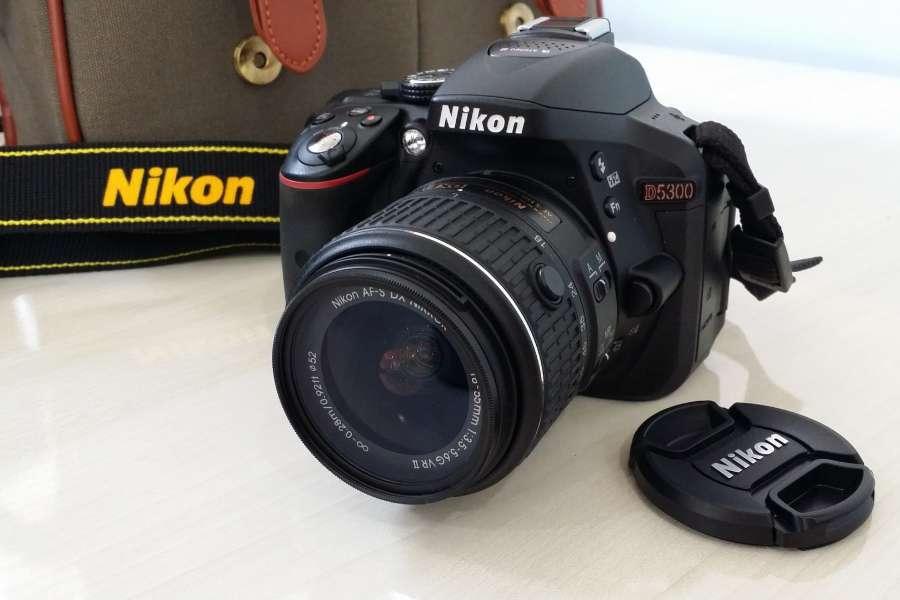 Nikon D5300 camera on a white table beside a bag