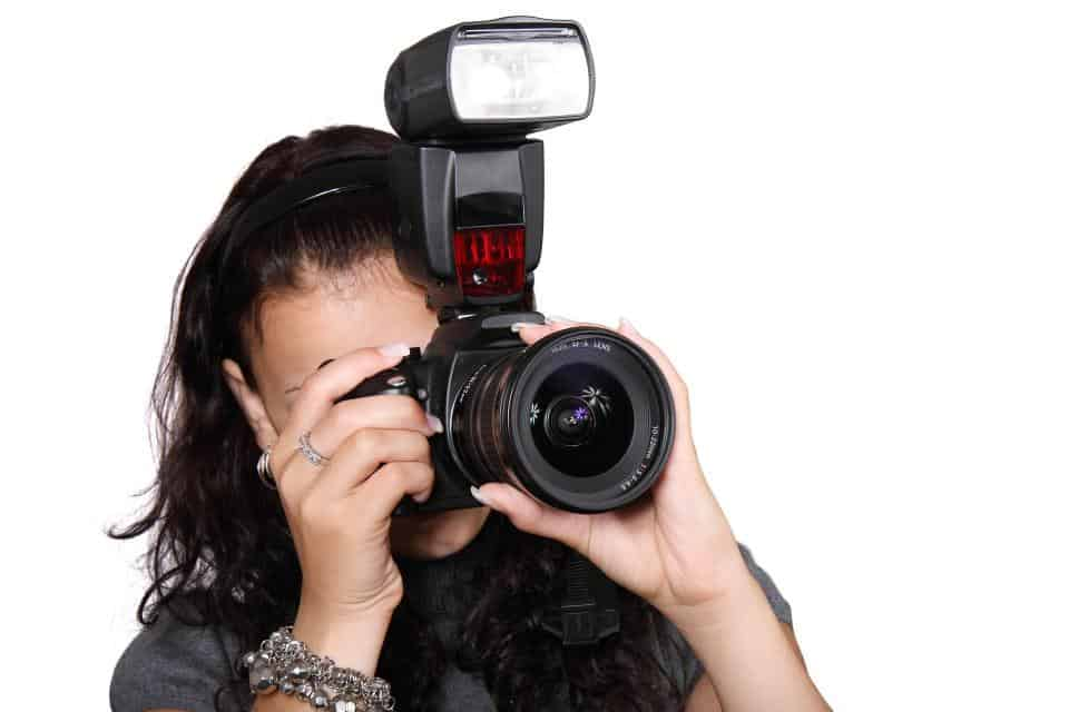 Woman taking a photo using a camera with flash