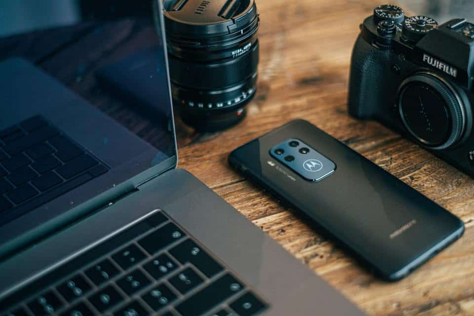 Camera and smartphone beside laptop