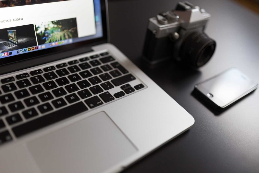 Phone and camera beside laptop