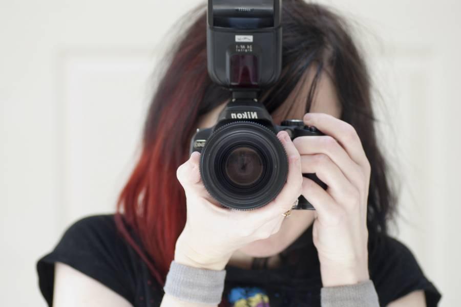 A girl using a Nikon camera with external flash