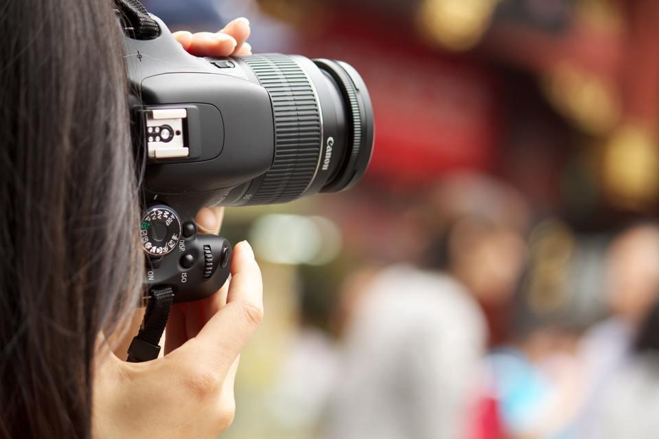 Woman taking photos using a Canon DSLR camera