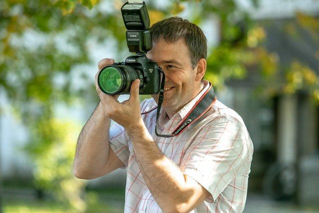 Man smiling while taking photos